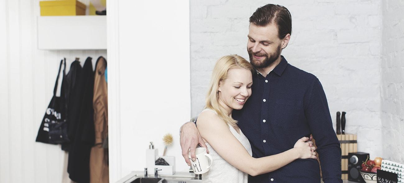 Ungt par holder rundt hverandre på kjøkkenet