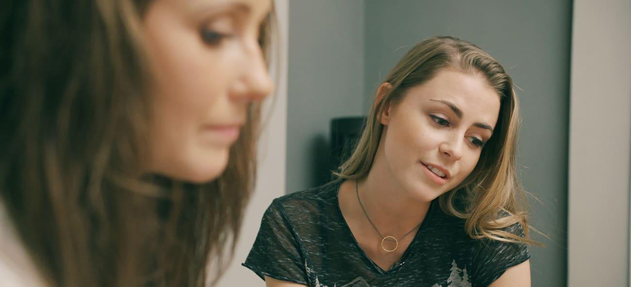 To kvinner ser ned på et skjema