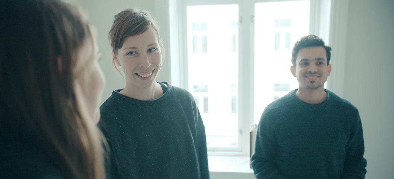 To kvinner og en mann står i en stue og smiler