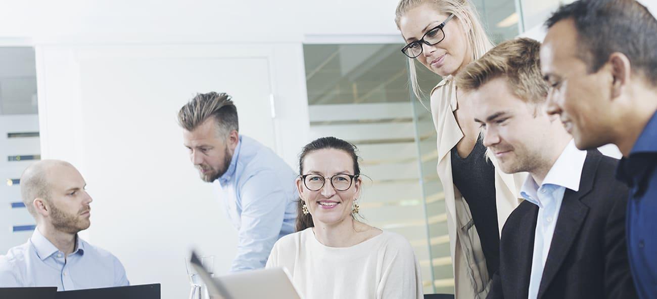 fire menn og to kvinner i møtesituasjone hvor en kvinne ser rett i kamera