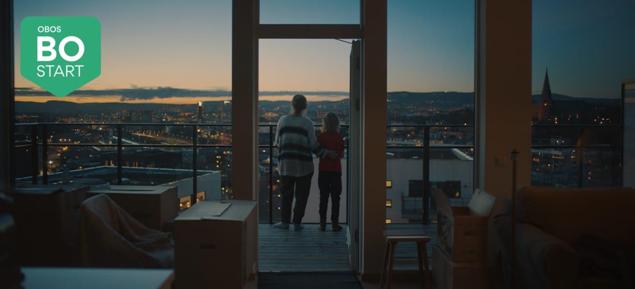 Mor og datter ser på utsikten utover byen fra sin nye bolig
