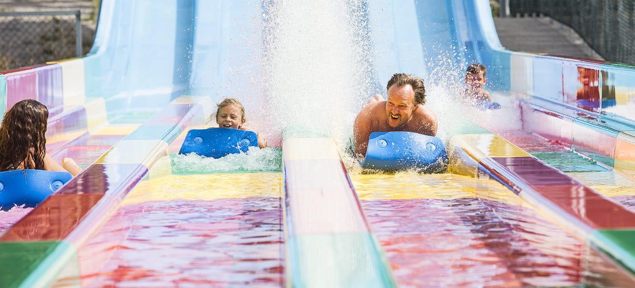 Datter og far sklir på magen i vannsklie