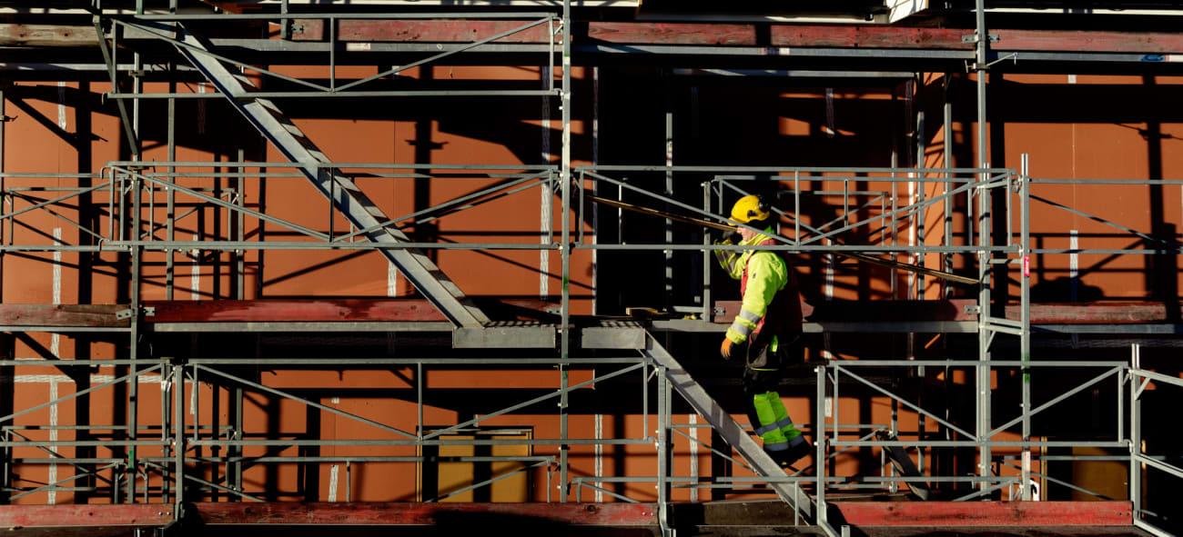 Bilde av tømrer som går i stilaset rundt et nybygg