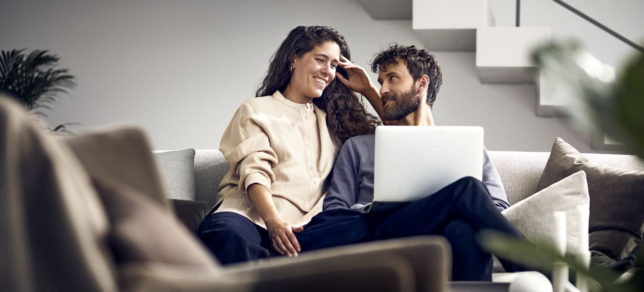 Mann og kvinne i sofaen med pc på fanget