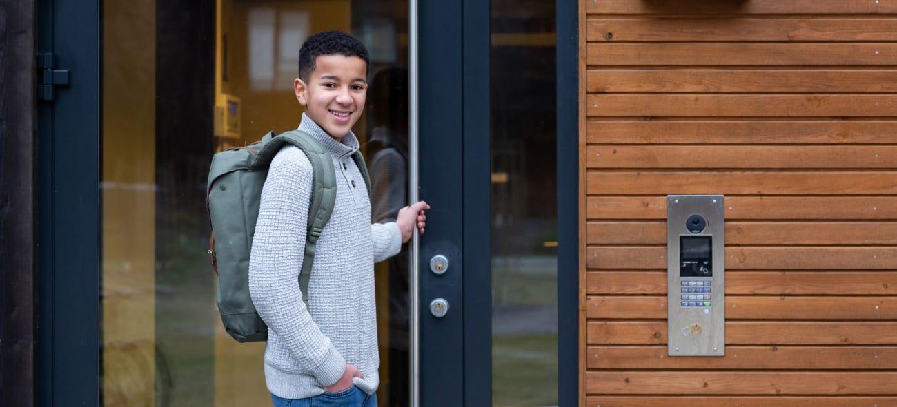 Gutt son holder i en utgangsdør