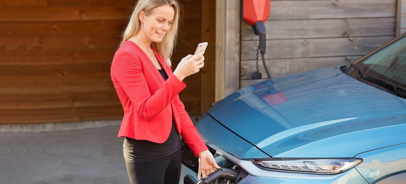 Kvinne lader bilen sin