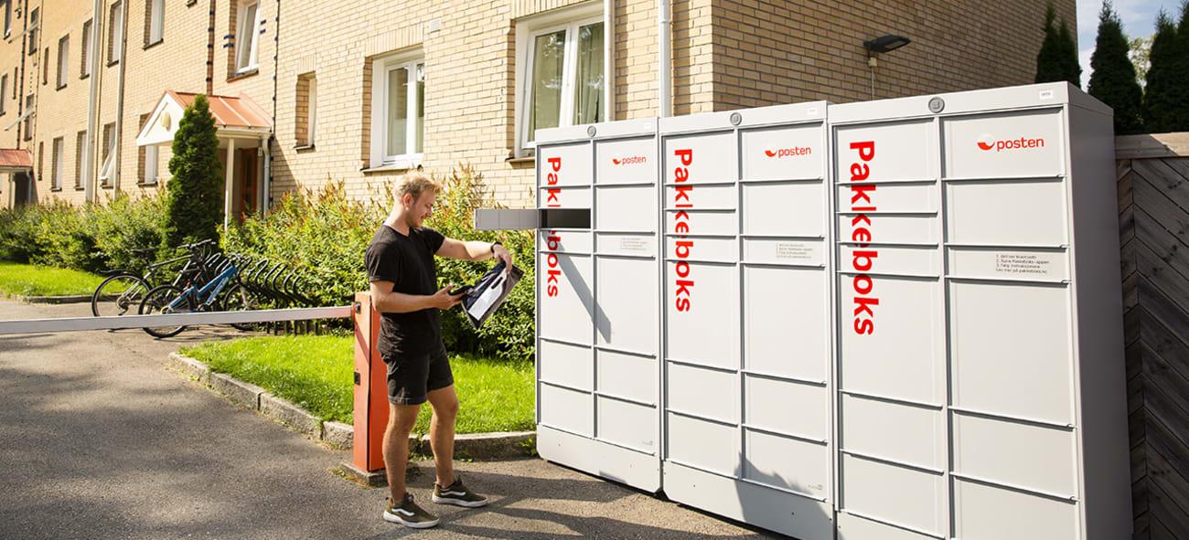 En mann ser på en pakke han har tatt ut av en pakkeboks uten for blokka han bor i.