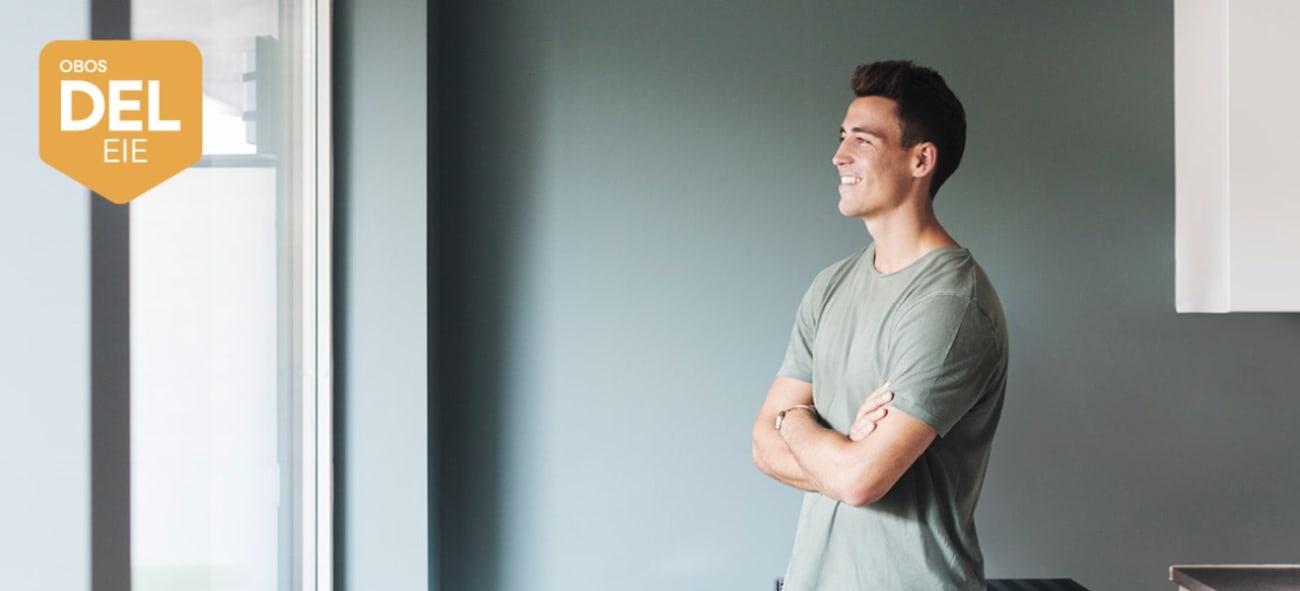 Illustrasjonsfoto av en ung mann i en leilighet. Bildet viser også OBOS Deleie-logo.