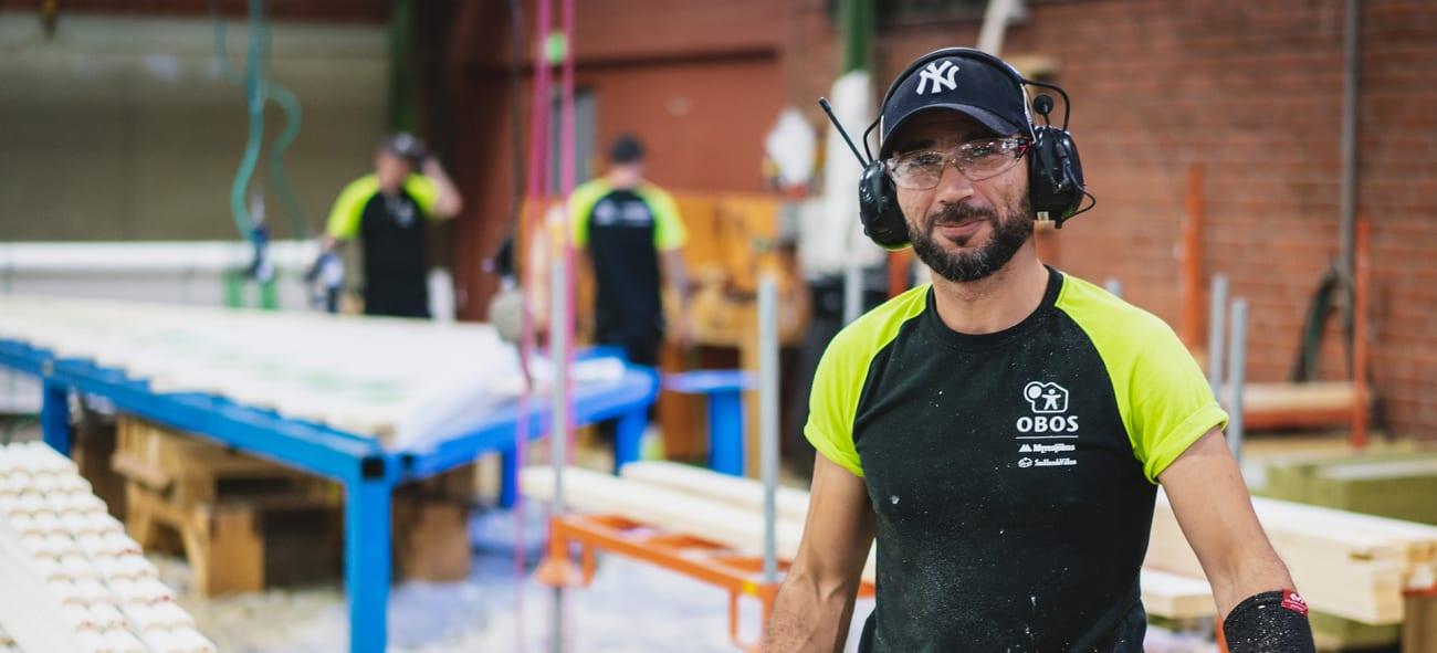 En kille står i arbetarkläder och skyddsglasögon i en OBOS-fabrik