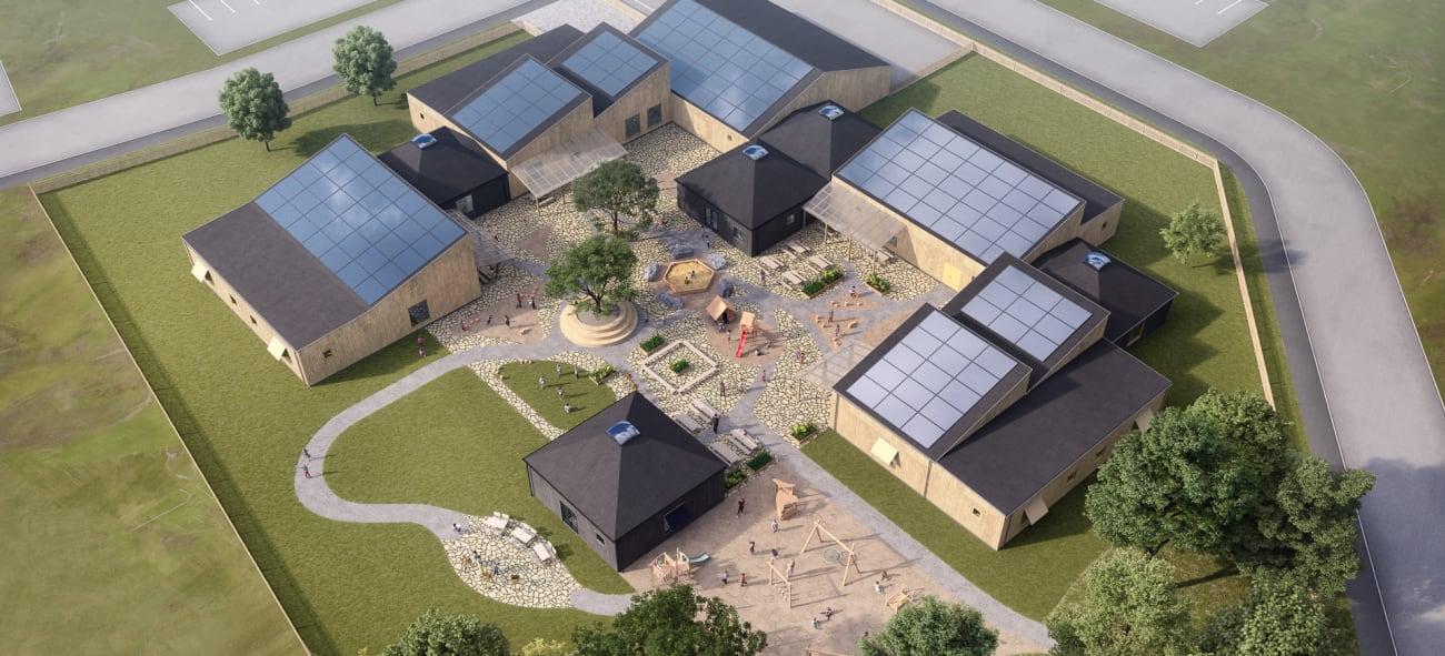 Helikoptervy över OBOS förskola med lekplats och solceller på taket