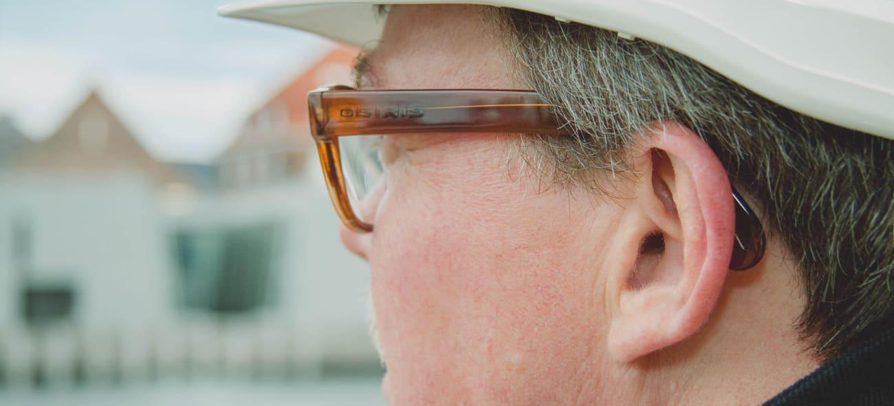 Man med bygghjälm och glasögon