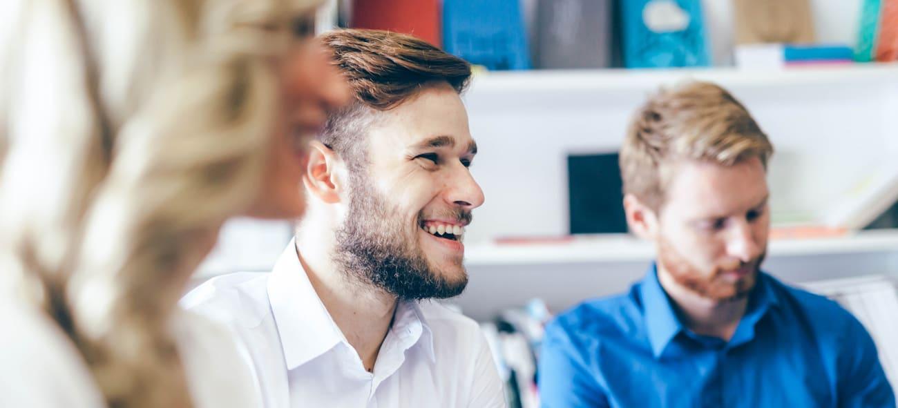 Män och kvinnor sitter skrattandes på möte