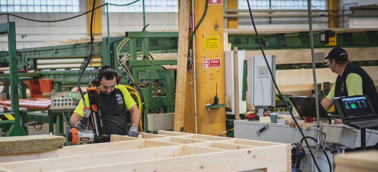 En arbetare som jobbar med trä i en obos-fabrik.