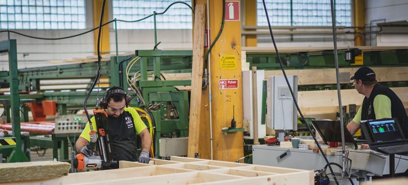 Två personer står och arbetar med trä-material i en fabrik