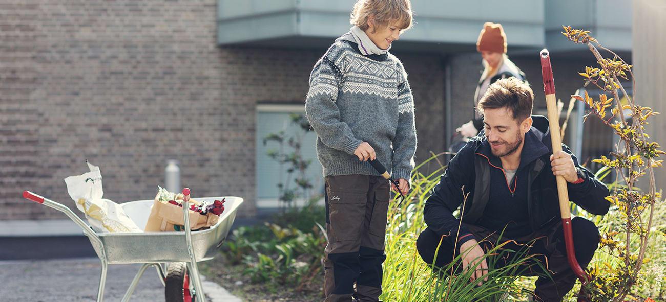 Illustrasjonsfoto av en gutt og en mann som deltar i dugnad i en bakgård.