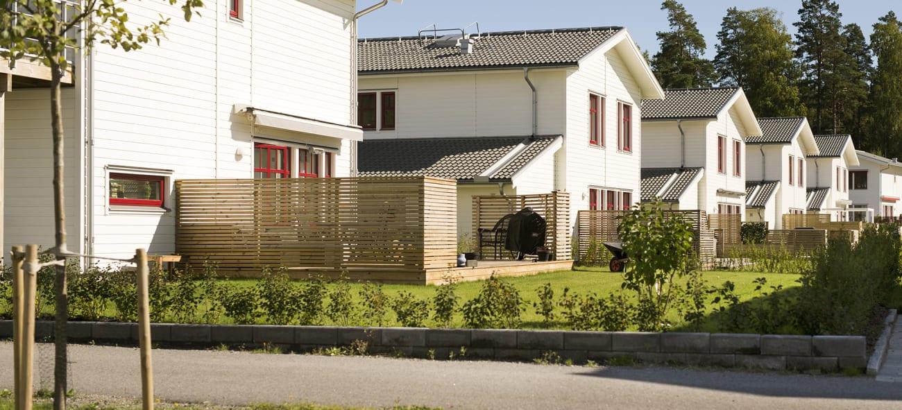 Bild på radhusområde med gröna trädgårdar och vita hus.