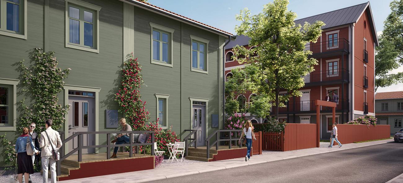 Gata med ett grönt och rött lägenhetskomplex, människor är ute i det fina vädret.