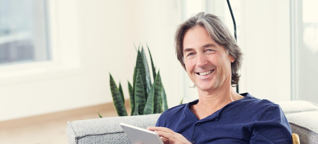 Mann sitter med nettbrett og sender inn forslag til OBOS