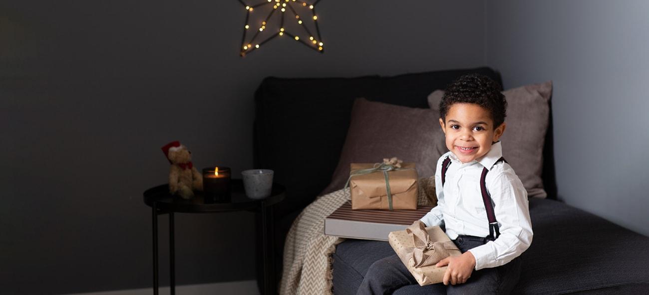 Ung gutt på soverom med julegave i fanet