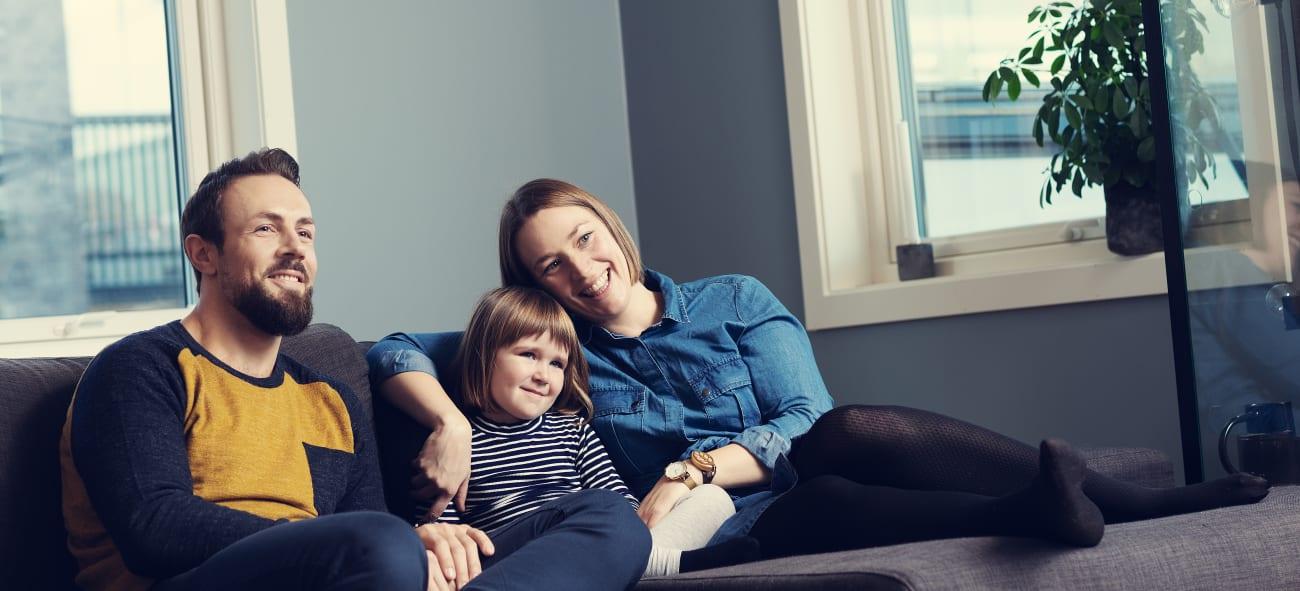 Familie sitter sammen i sofaen og ser samlet på noe