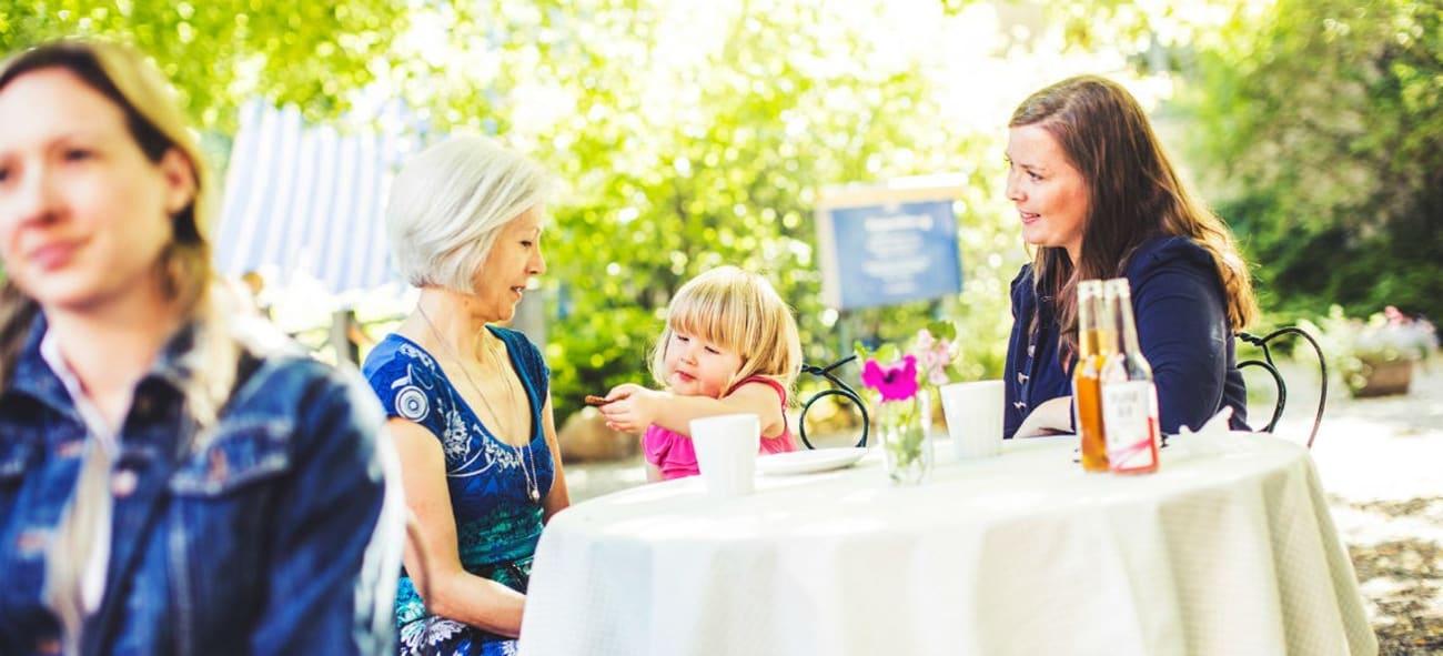 Morfälder med barn och barnbarn samlade utomhus vid runt bord med vit duk.
