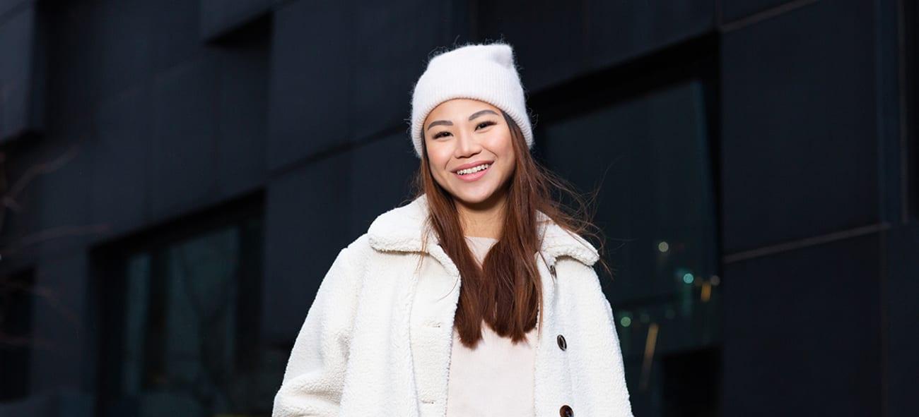 Ung kvinne med hvit lue og jakke smiler til kamera foran mørk bygning