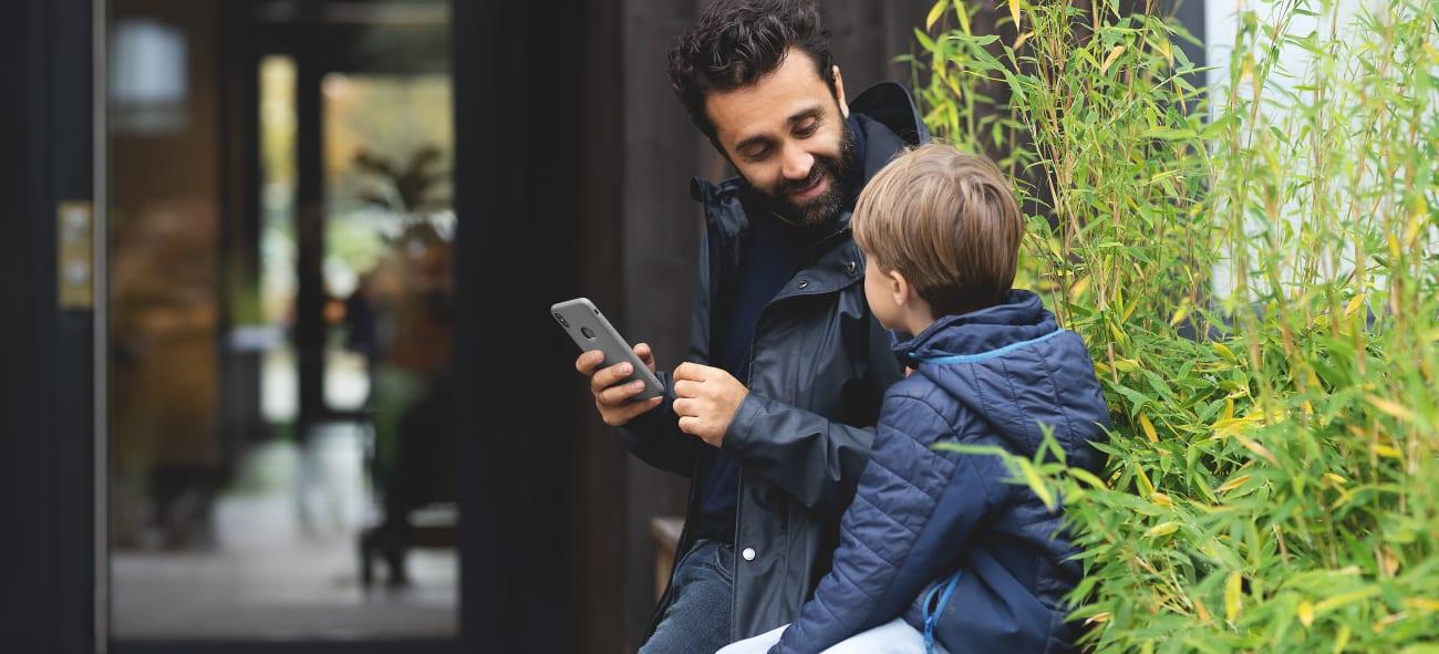 Pappa og sønn sitter utenfor utgangsdøren med en telefon