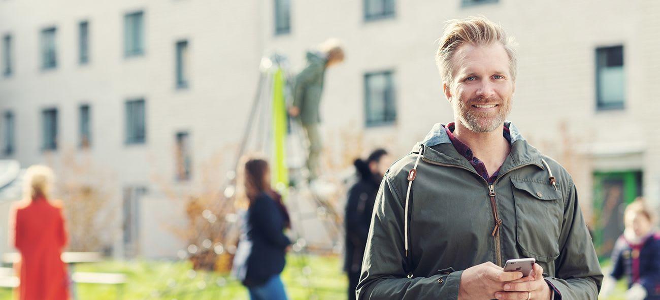 en kille står med en mobiltelefon i handen
