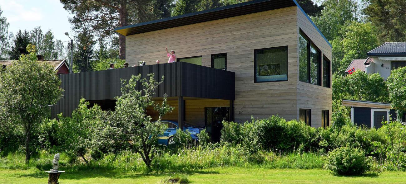 Et hus over to plan med funkis-inspirert stil, carport og store vinduer.