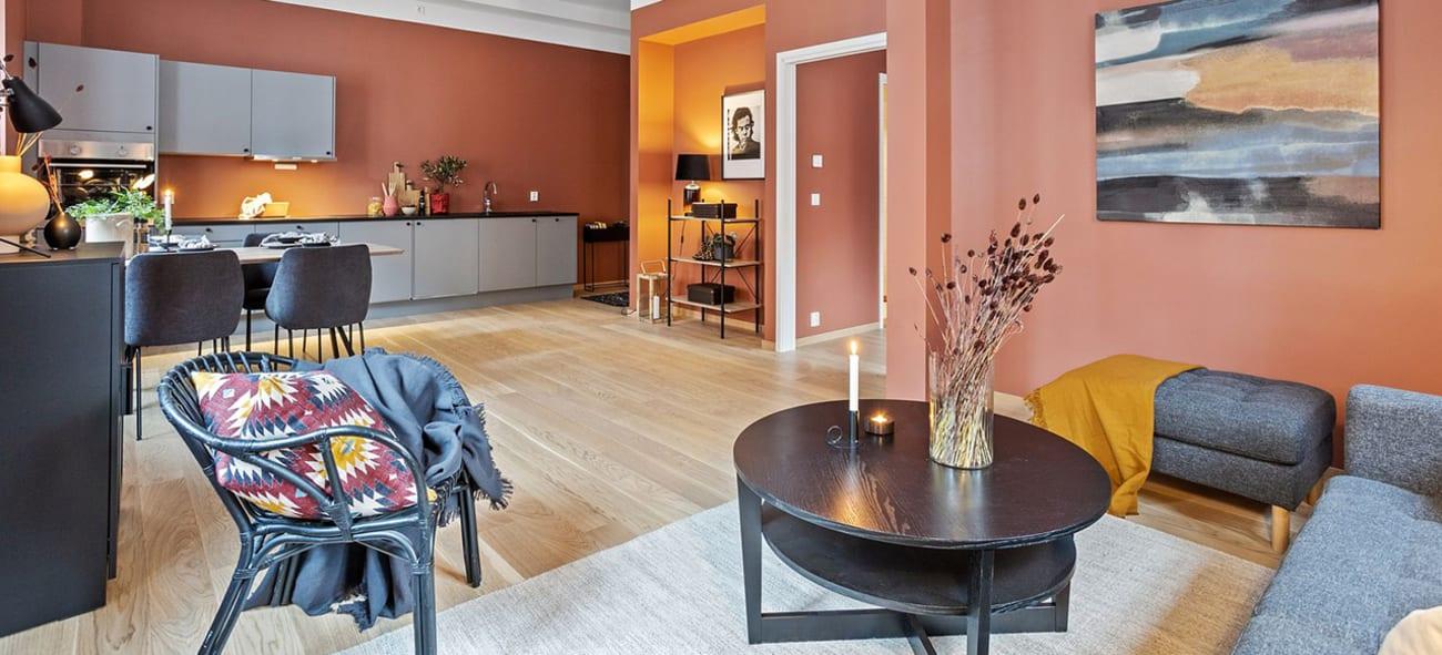 Stue og spiseplass ved kjøkken i Kværerdammen i leilighet med god takhøyde.