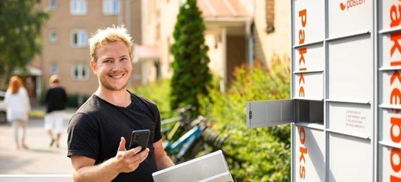 Mann med mobil står ved en pakkeboks med en pakke i hånda