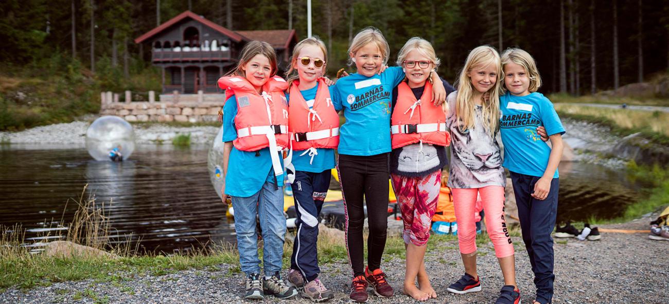 seks barn med redningsvester foran et vann