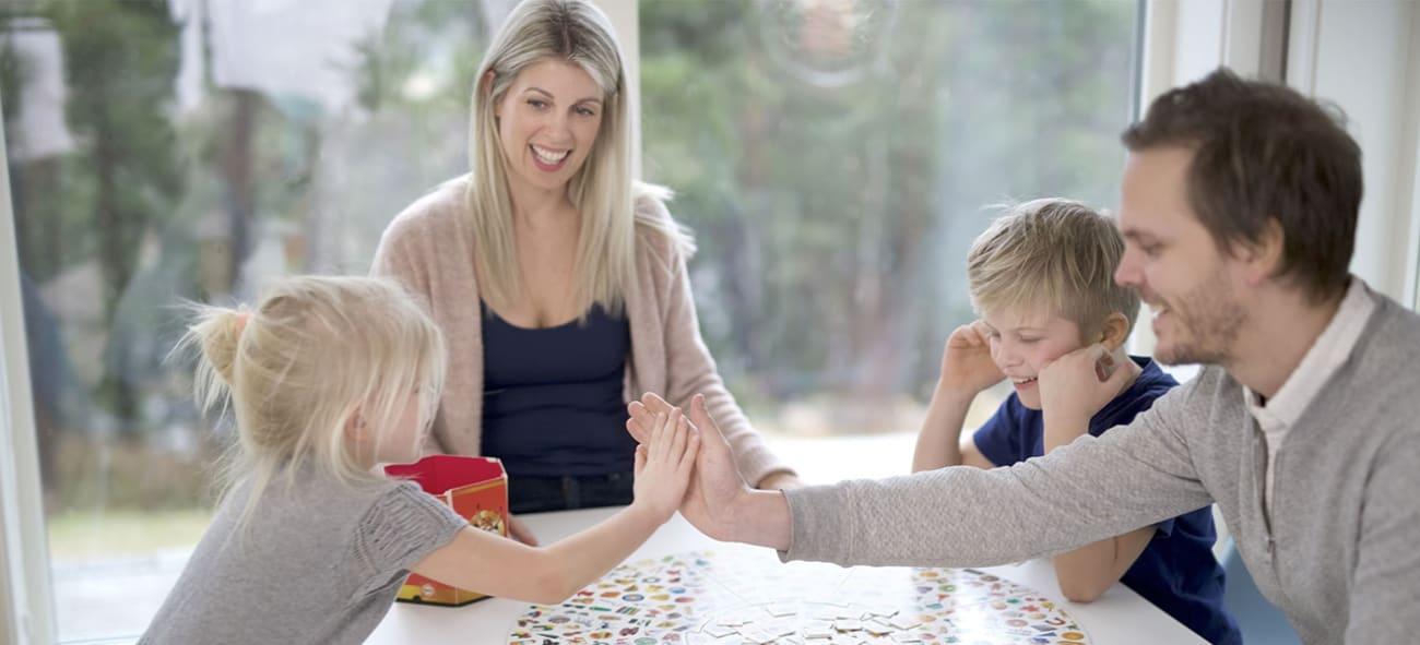 Familie på fire med en mor, en far og to barn sitter rundt et bord og spiller et spill.