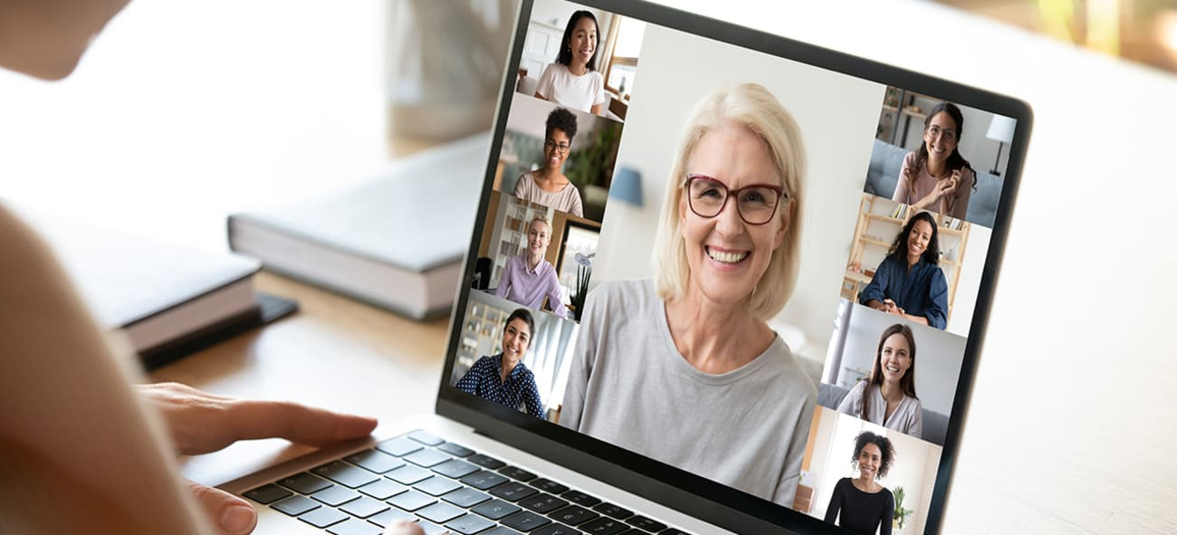 En dame ser på pc hvor det er et digitalt møte