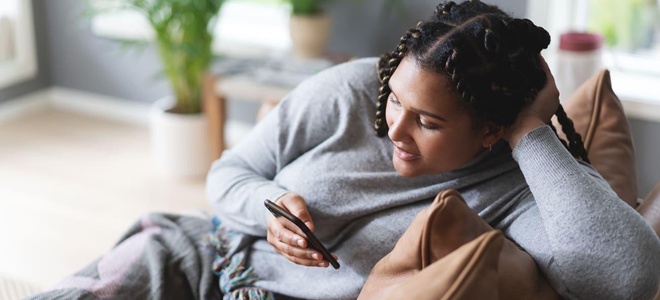Illustrasjonsfoto av ung kvinne i en sofa som ser på mobilen sin.