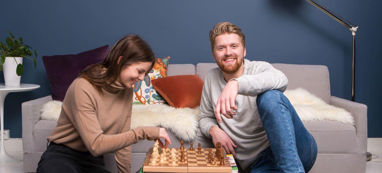 Ungt par spiller sjakk på gulvet foran en sofa