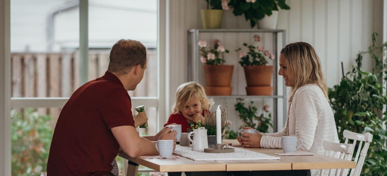 En familj som sitter och fikar