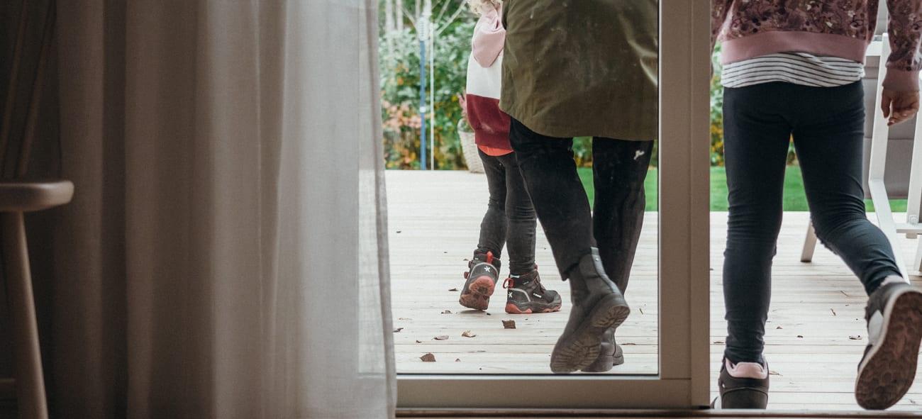 Två barn som är på väg ut i trädgården