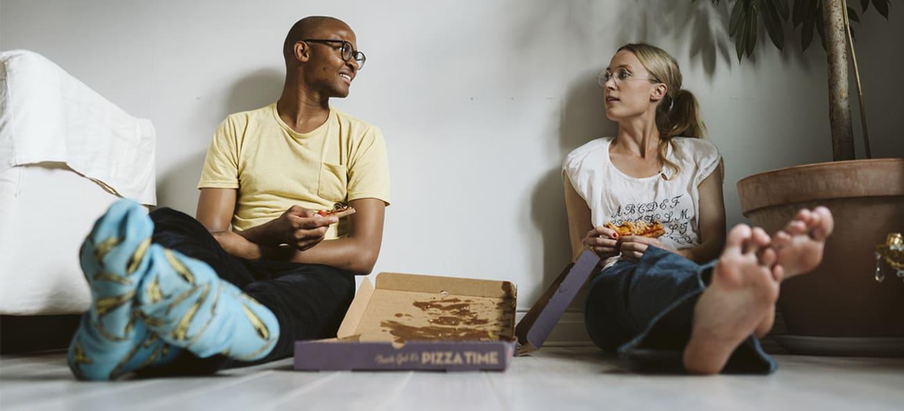 Et par spiser pizza på gulvet i ny leilighet