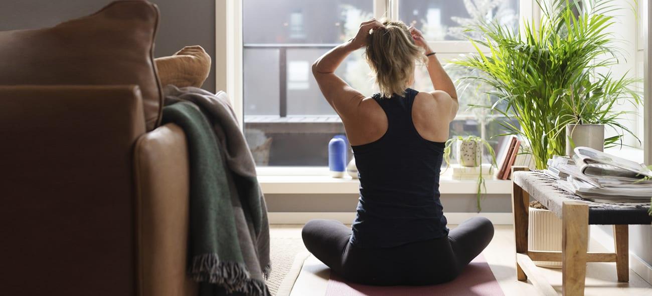 Dame gjør yoga foran et vindu