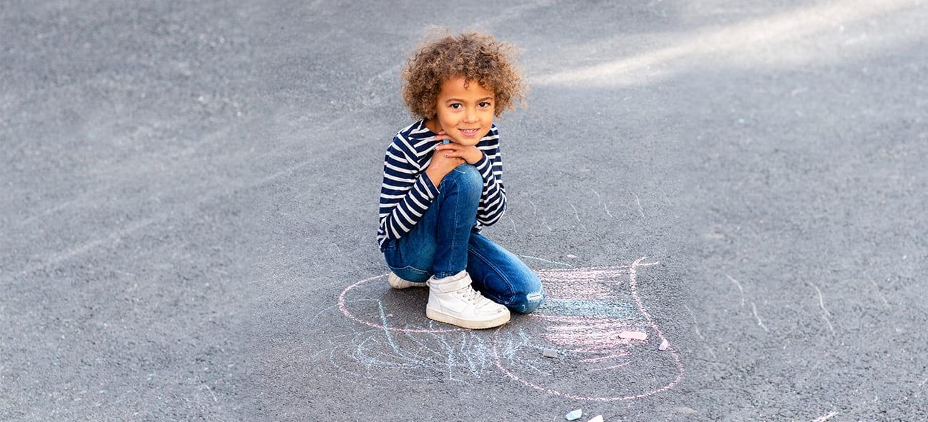 Jente sitter på asfalt med krittegning