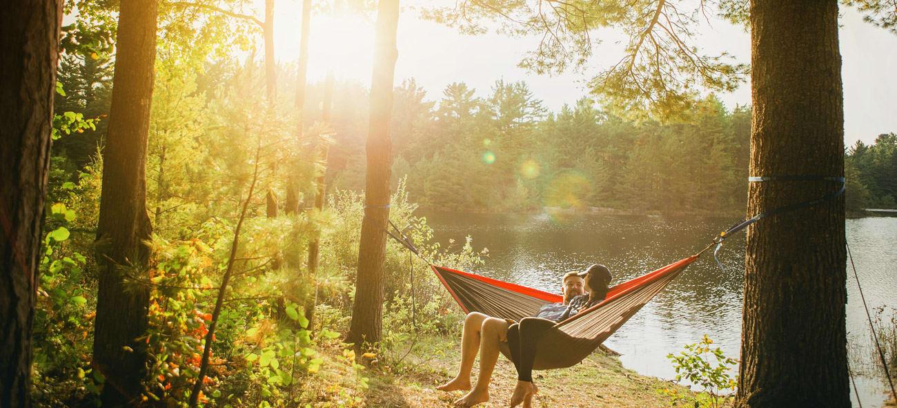 Et par sitter i en hengekøye i en skog ved et vann i solnedgangen