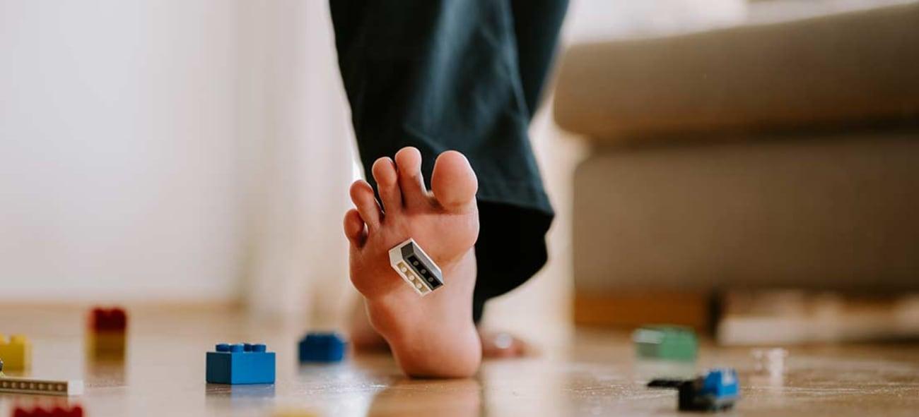 Bilde av føttene til en person som er på vei til å tråkke på en legokloss.