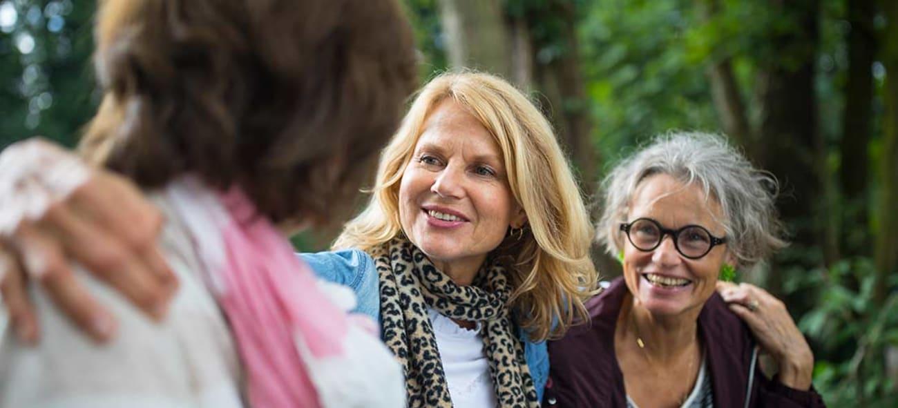 Tre eldre damer holder rundt hverandre og smiler.