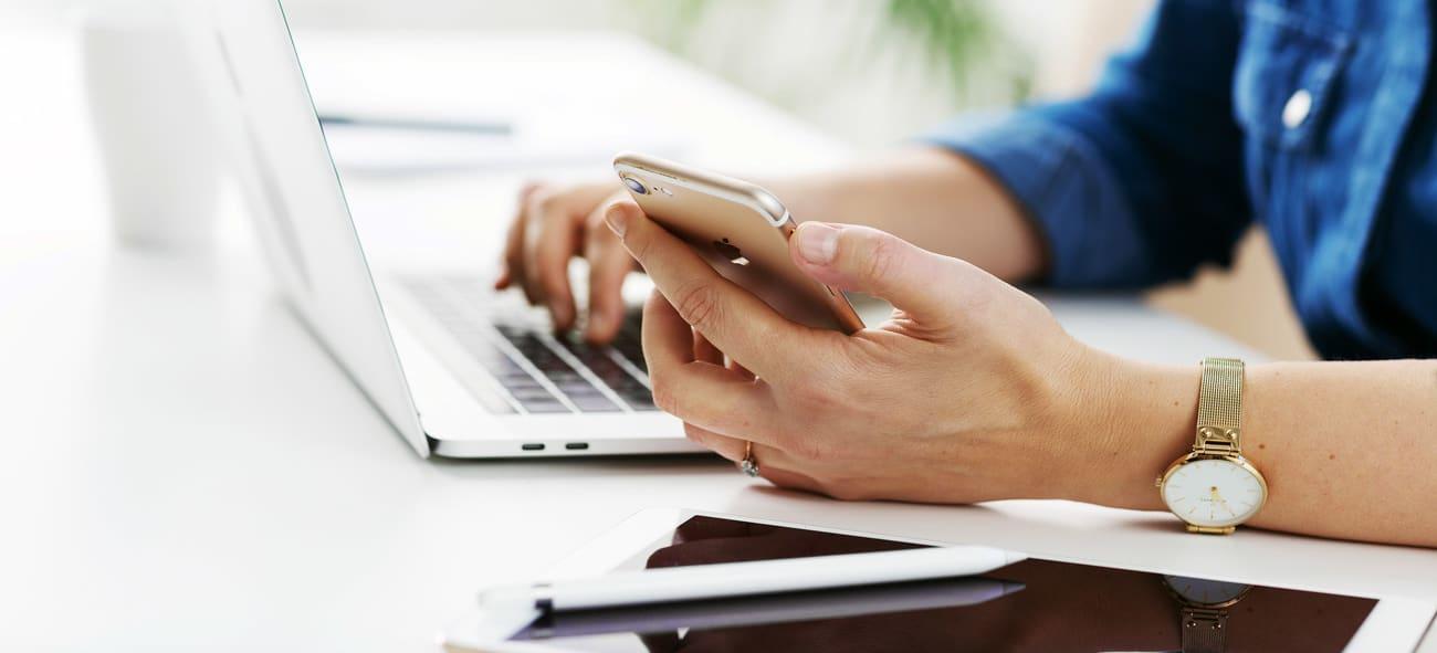 Nærbilde av hender som sitter med en pc og en mobiltelefon