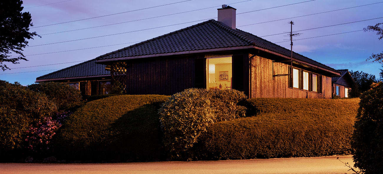 Bilde av et brunt trehus med busk rundt tatt på kveldstid.