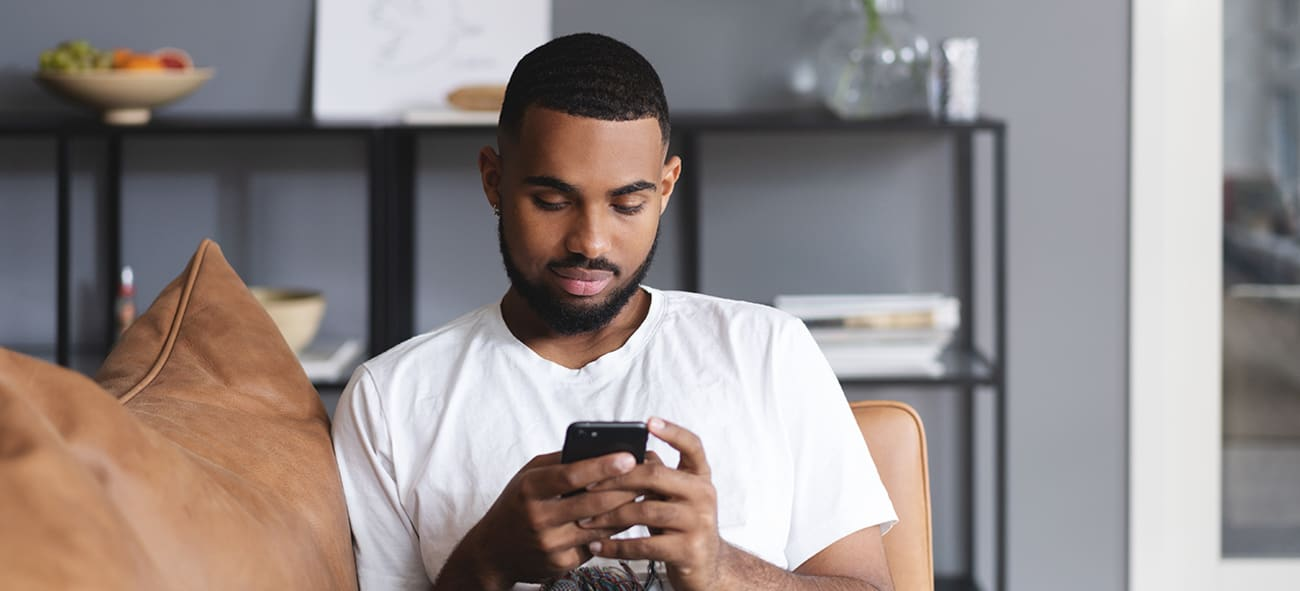 Ung mann ser på mobilen i en sofa.