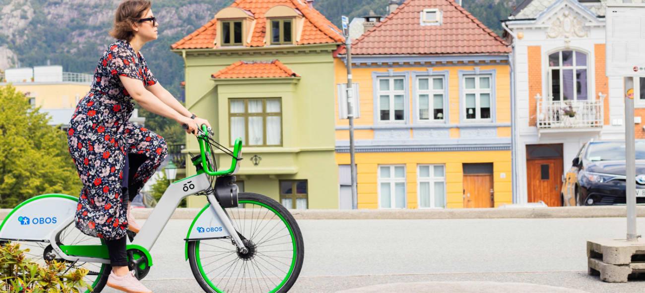 Dame på en grønn bysykkel med hus i bakgrunnen