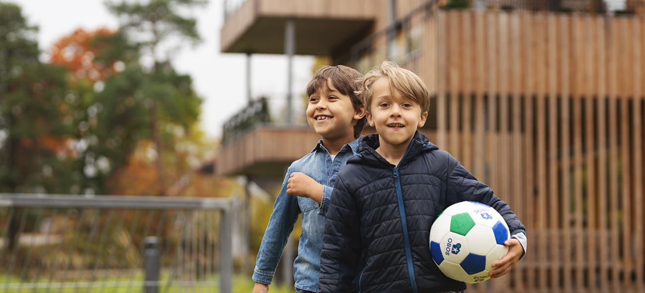 To gutter som spiller fotball i et OBOS nabolag