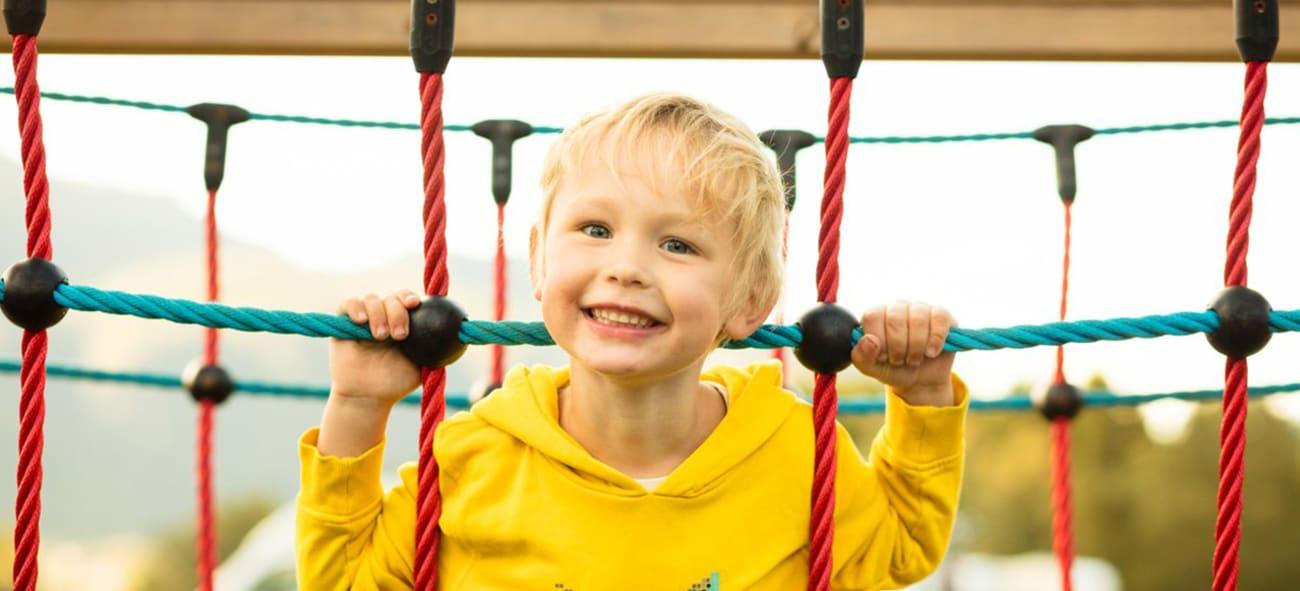 Smilende gutt i et lekestativ.